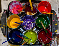 Nine buckets of paint with a paint brush in each
