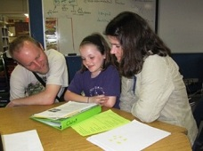 A CS student shows off her work to her parents.